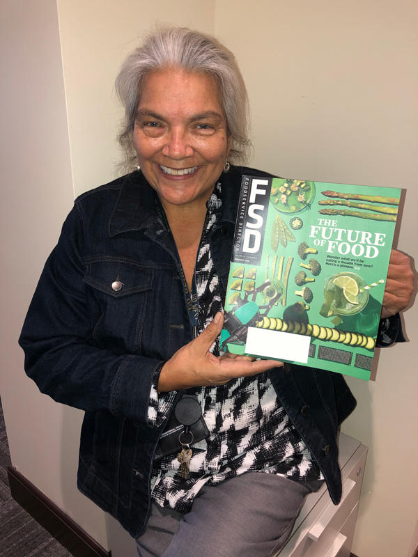"""Maureen Spolidoro, I-House Dining Supervisor, holds a fresh copy of """"The Future of Food"""" where I-House is featured"""